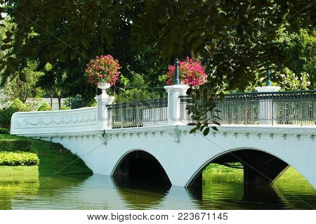 A white footbridge with arches, and metal railings stretches over a lake in a park. Bright flowers in pots are on the bridge. A tree frames the foreground. Lush lawn runs down to the water. A white wall is the background.
