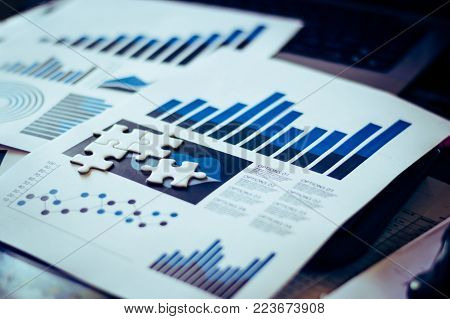 Four pieces of jigsaw puzzle on lay on data report of businessman table for business solution and success concept,selective focus