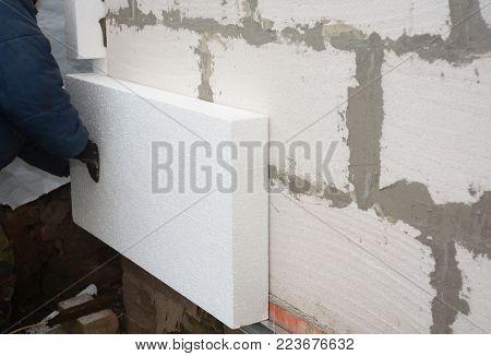 Builder Installing Rigid Styrofoam Insulation Board For Energy Saving. Rigid Extruded Polystyrene In