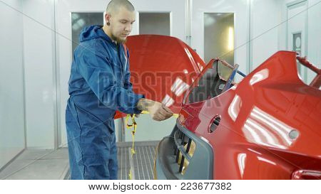Car bumper after painting in a cars spray booth. Auto vehicle primer bumper. Repairer removes protective film after paint parts. Parts of car in cars spray booth.