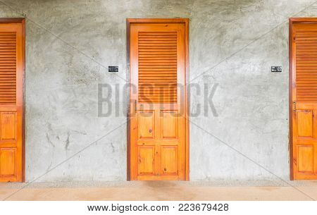 Classic or retro doors for interior design or exterior design. Brown bathroom doors with concrete wall. Vintage doors in cinematic mood.  Doors and switch and concrete wall in roft style.