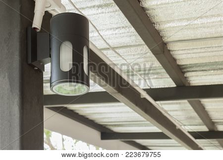 Black wall lamp under the roof for interior design or exterior design. Cylinder wall lamp. Wall lamp in modern style. Wall lamp and electric  wire under structure