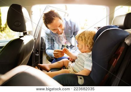 Father putting his son in the car. Toddler boy sitting in a car seat.