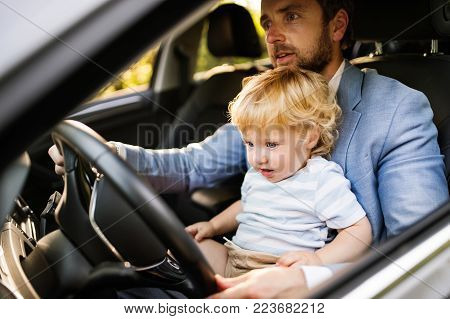 Man driving a car with little son. Toddler boy sitting in his fathers lap.