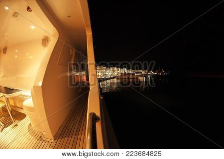 A scenic night view from a yacht. The black night sea and sky, another yachts at a wharf, buildings, a little bit illuminated by lamp posts on a promenade. Everything sleeps, no one is here.