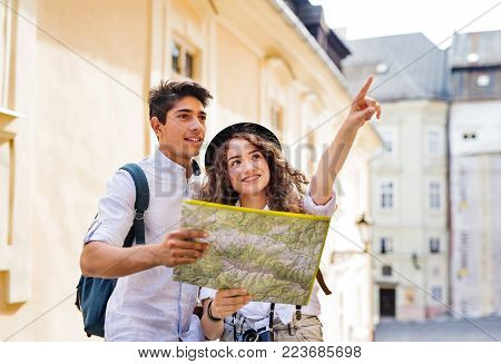 Two beautiful young tourists with map and camera in the old town