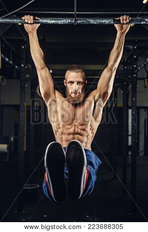 Muscular brutal man with beard doing pull up on horizontal bar in a gym.
