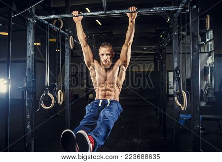 Bodybuilder with beard doing pull ups on horizontal bar in a gym.