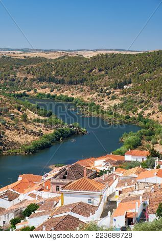 View of Guadiana river bend and residential houses of Mertola city on the riverside as seen from the Castle hill. Mertola. Baixo Alentejo. Portugal