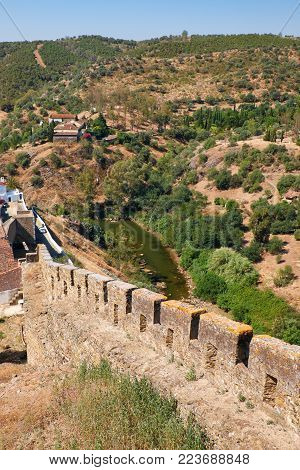 The defensive wall with battlements which encloses an area of the old town  Mertola. Baixo Alentejo. Portugal