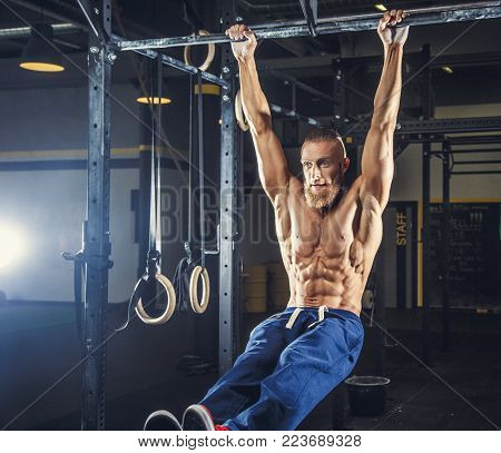 Shirtless muscular man in blue sports pants doing exercises in a gym on horizontal bar.