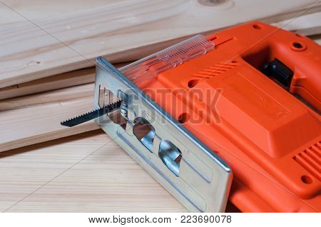 Orange elctric jig saw and wooden planks on a work table