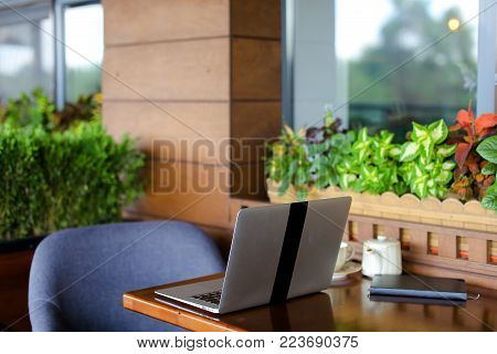 Close up laptop on restaurant table without people. Teapot, cup and black notebook at catering establishment. Concept of working place at cafe and modern gadget.