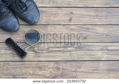 old shabby black shoes sleep laces. shoe  and old shoe brush. on a wooden background. view from above
