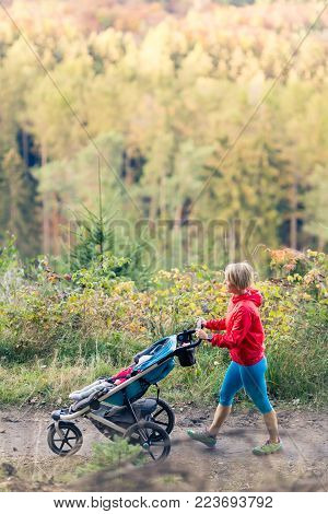 Walking mother with child in stroller enjoying motherhood at autumn sunset and mountains landscape. Jogging or power walking woman with pram in woods. Beautiful inspirational mountains landscape.