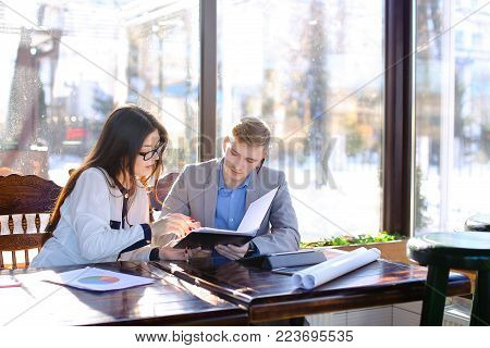 Pretty female secretary speaking with businessman at cafe and giving black document case. Young man sitting at cafe with beautiful woman in glasses. Concept of business meeting at catering establishment.