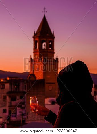 A Young Woman In The Hood, She Taste The Single Malt Whisky On The Terrace, View Of The Church Tower