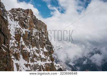 view of rocky slope with snow against clouds in sky, Ala Archa National Park, Kyrgyzstan