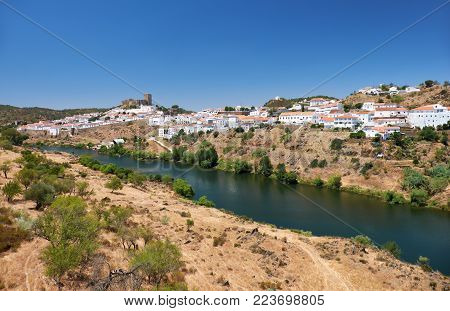 Mertola with the old mediaeval castle on the hill as viewed from the high opposite side of the Guadiana river. Baixo Alentejo. Portugal