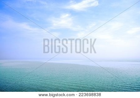 Fluffy clouds on clear blue sky with blue seascape in summer sunny day.