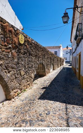 The arches of the aqueduct of Silver Water (Prata Aqueduct) lowers and getting surrounded with shops and houses as they enter Evora. Portugal
