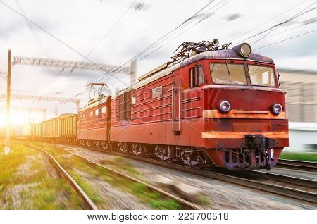 Red locomotive electric with a freight train at high speed rides by rail