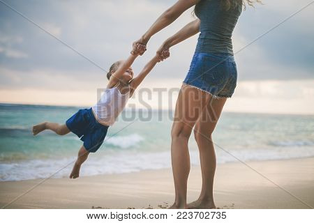 Mother turns her daughter by the arms. Happy Mom and happy child traveling to Asia, at the beach. Traveling with your family, child. Important to spend enough time with your kids.