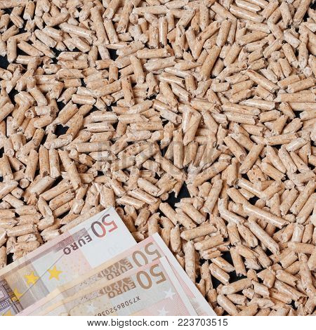 Wood pellets for heating and money.  Money saving concept. Square composition.