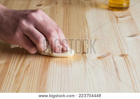Hand oiling a wood Surface. Horizontal composition.