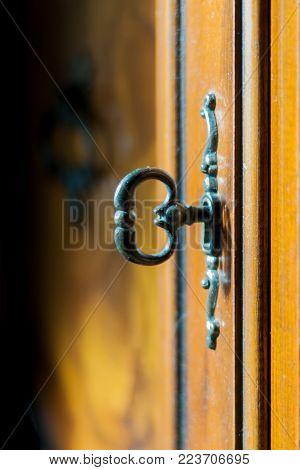 Closeup of the metallic key of an antique wood furniture