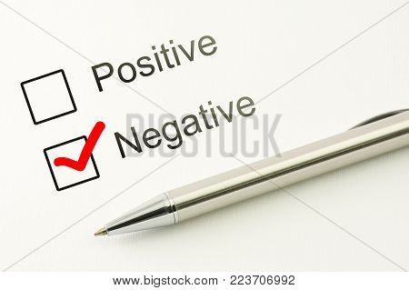 questionnaire: negative choice or positive, marked checkbox with a silver pen on paper background closeup. Disapproval concept