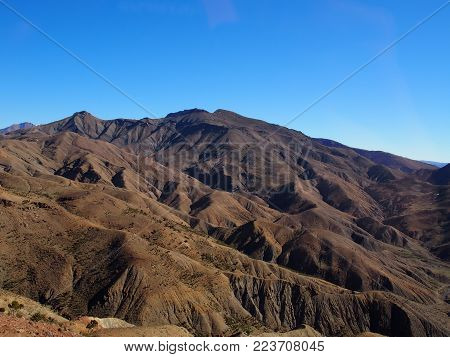 High ATLAS MOUNTAINS range landscape in MOROCCO seen from location near Tizi-n-Tichka pass in central part of country with clear blue sky in 2017 warm sunny winter day, northern AFRICA on February.
