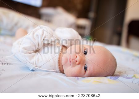 The baby is lying on the bed. Lovely beautiful baby. A small toddler is looking intently.