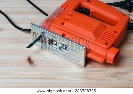 An orange elctric jig saw on a wooden table