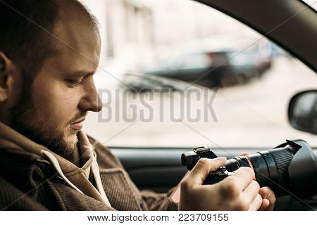 Investigator or private detective or reporter or paparazzi sitting in car and taking photo with professional camera, toned