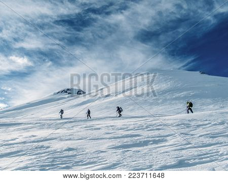 side view of hikers climbing at beautiful snow capped mountains, Russian Federation, Caucasus