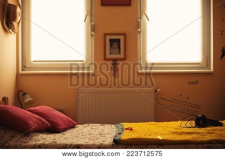 Interior of a teenage girl, closeup view on bed besides windows and various personal things and lifestyle objects.