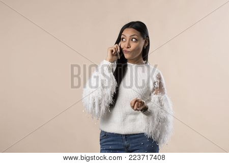 young arabic latina woman talking on the phone isolated on studio background