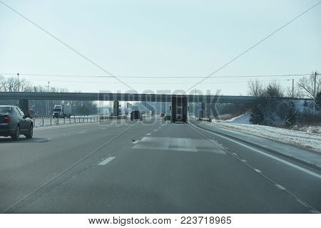 Interstate I-75 in Ohio in winter with overpass and snow by the side of the road
