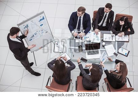 top view:businessman pointing the marker on the Board with financial schedules and business team sitting on workplace
