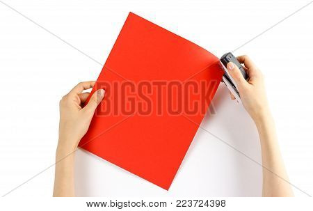 Fasten the red paper with staples on a white background. Closeup.