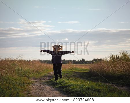 The little girl quickly runs through the vast field. The child is happy