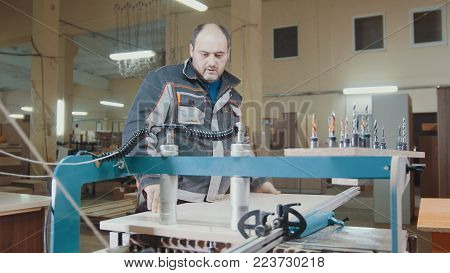 Worker carpenter cut a wooden workpiece on a furniture factory, woodworking