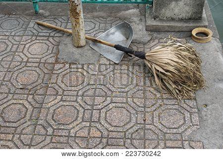 Rustic broom and dustpan on tiled sidewalk in Hanoi Vietnam