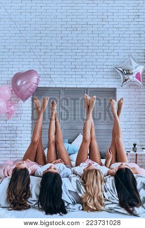 Irresistible girls. Playful young women keeping feet up while lying on the bed with balloons all over the room