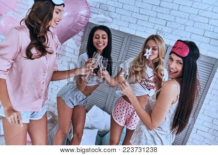 To our friendship! Four attractive young smiling women in pajamas toasting each other while having a slumber party in the bedroom
