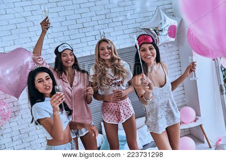 Magic trick. Top view of four attractive young smiling women in pajamas drinking champagne while having a slumber party in the bedroom with balloons all over the place