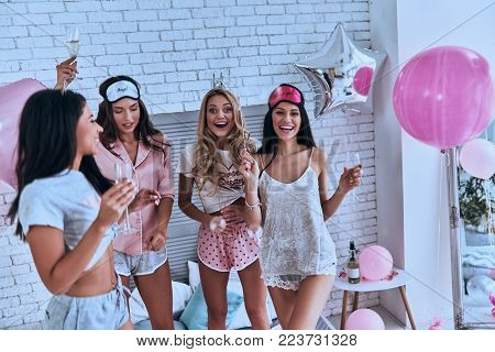 Gorgeous beauties. Four attractive young smiling women in pajamas drinking champagne while having a slumber party in the bedroom with balloons all over the room