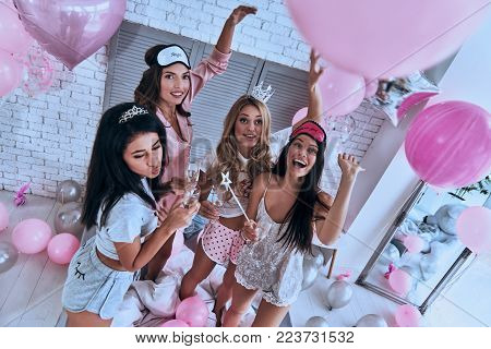 Ladies party! Top view of four attractive young smiling women in pajamas drinking champagne while having a slumber party in the bedroom