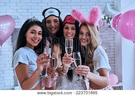 Cheers! Four playful young smiling women in pajamas toasting each other while having a slumber party in the bedroom with balloons all over the place